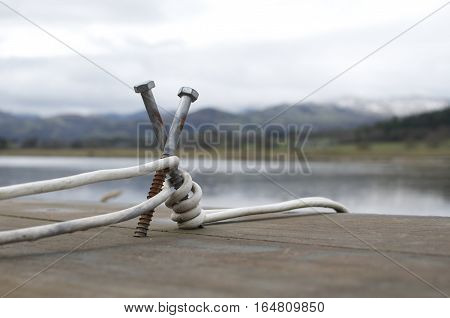 Rustic makeshift mooring bollard with white rope cable snow capped mountains in the background