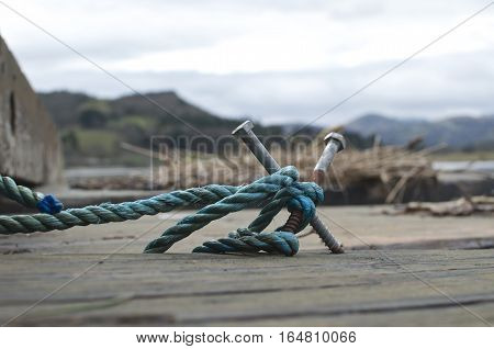 Rustic makeshift mooring bollard with blue rope snow capped mountains and river in the background