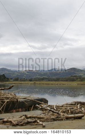 Snowdonia, Snow capped mountains, reflection in the water behind a tranquil river view with wooden jetty with sticks and twigs portrait