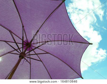 Purple colored parasol under vivid blue sky with white cloud