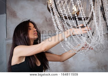 Pretty young woman choosing the right chandelier for her appartment in a vintage home