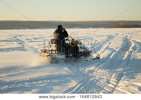 Young Man Posing On Snowmobile At Winter Day