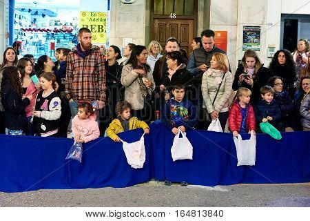 Torrevieja Spain - January 5 2017: Children waiting for a candies in Cavalcade of the Magi parade or The night of the Three Wise Men in downtown of Torrevieja. The Cavalcade of Magi attracts thousands of visitors every year.