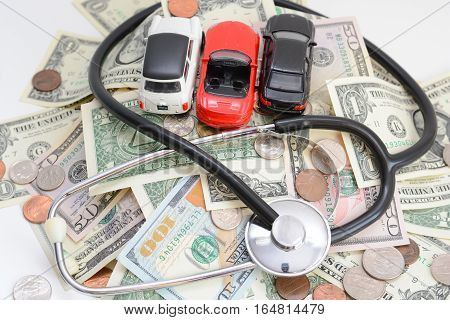 Automotive industry analysis concept with toy cars and stethoscope on money