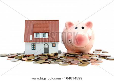 Piggy bank and model house on cash suggesting savings for house