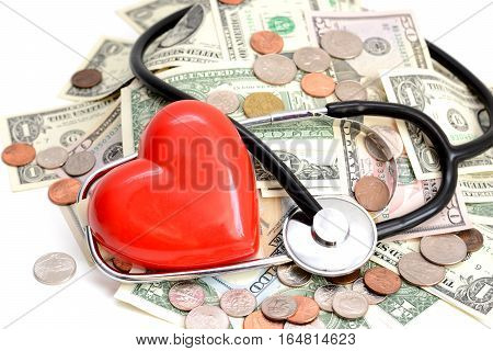 Red heart and stethoscope resting on pile of dollars