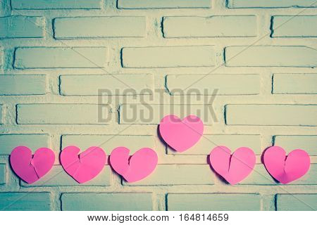 Pink sticky notes broken hearts shaped lined holes on the wall and a heart the outstanding one. vintage style