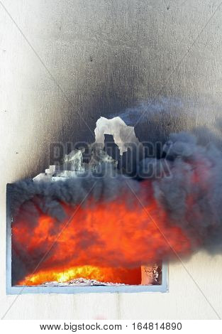 Photo of huge flame distracting house on fire. Fire safety concept