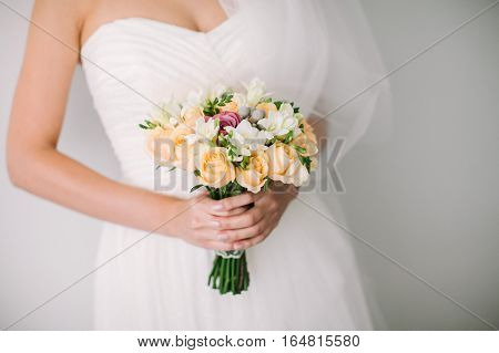Beautiful woman in a wedding dress. Wedding bridal bouquet on a white background. The bride holds a fine wedding bouquet in hand.
