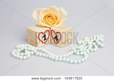 Wooden cubes with handwritten 14th and red hearts, yellow rose and beads.