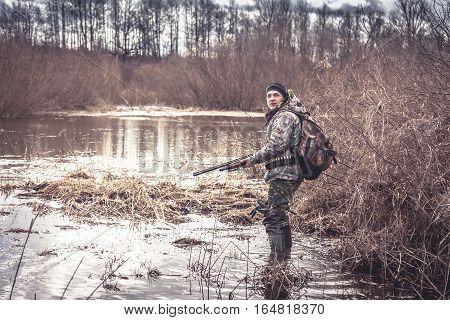 hunter man creeping in swamp during spring hunting season