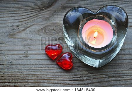 Heart shaped candle holder with burning candle and two decorative red hearts.Saint Valentine's Day or love concept.Selective focus.