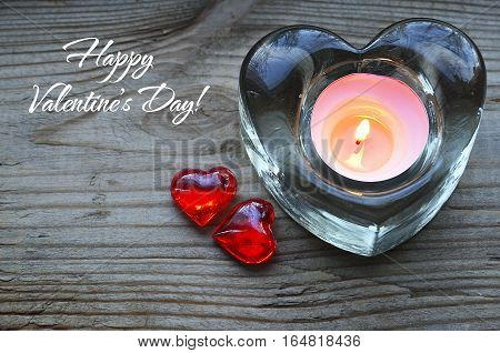 Happy Valentines Day background.Heart shaped candle holder with burning candle and two decorative red hearts.Saint Valentine's Day concept.Selective focus.