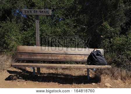At the end of the hiking trail, a backpack sits at the end of an empty wooden bench.