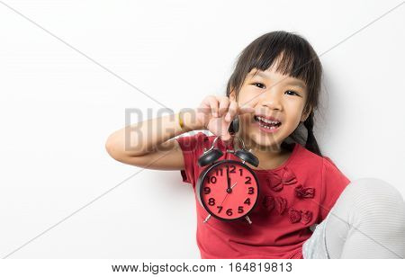 Happy girl is holding alarm clock counting for lunch time.