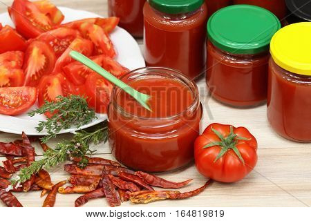 Homemade preserved ketchup. Jars of fresh ketchup at the background