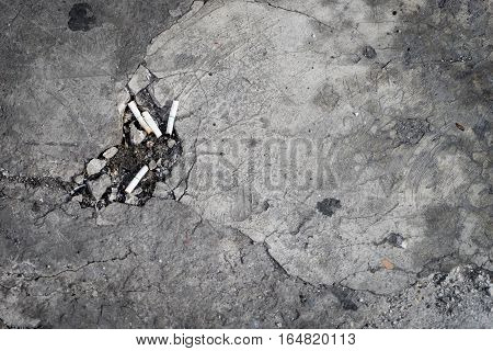 Cement Floor with a hole full of Cigarette butts