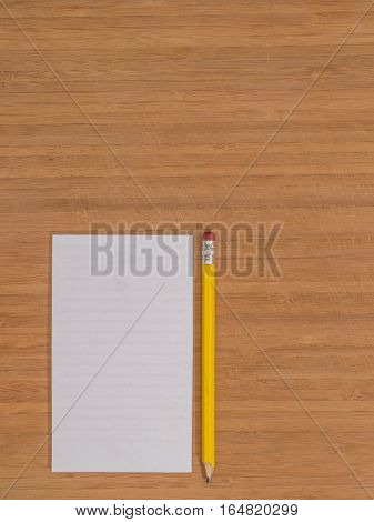 Bamboo desktop, white notepad, pencil, copy space