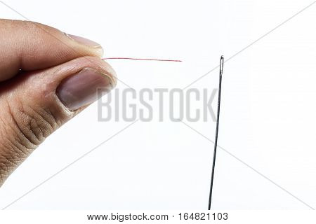 Hand Of Man Threading A Needle