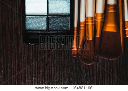Makeup brushes on the table were gold, and powder next