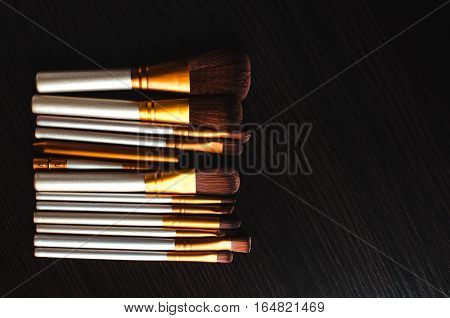 Makeup brushes on the table, dark were gold