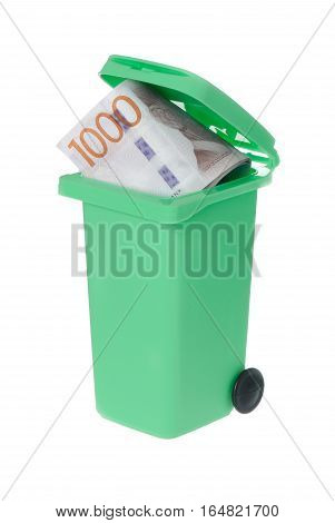 One green recycle bin with a wasted Swedish banknote 1000 krona visible inside isolated on white background.