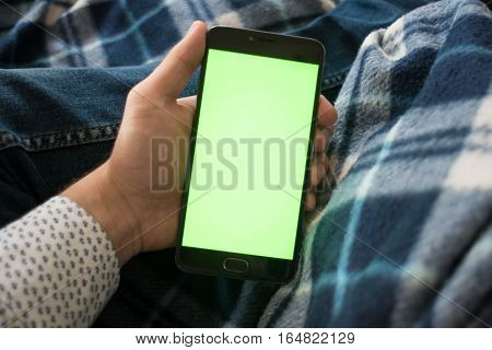 smartphone with green screen for key chroma screen In the hands of a man. On vintage blue bedspread