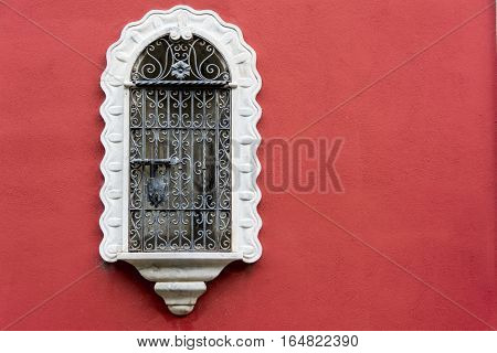 Antique medieval window with white iron bars and red wall in Seville, Spain