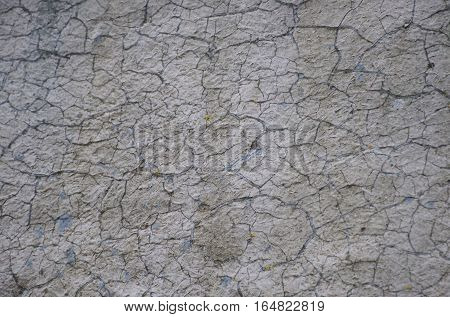 Cracked white with blue hints wall backdrop pattern with peeling paint and cracks Texture