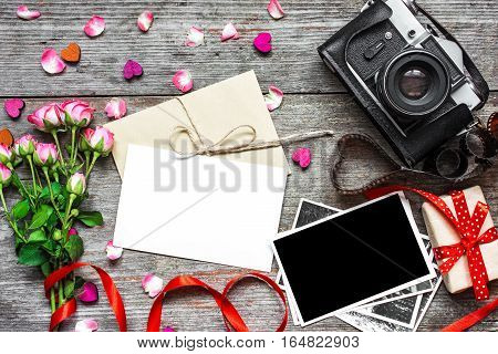 blank white greeting card with retro camera blank photo gift box and pink roses flower bouquet over wooden background. top view. valentines day background