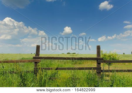 Country Timber Fence. Old wood fence with a green country field behind it. Wooden slit rail fence fades into the distance across a green field blue sky and white clouds above.