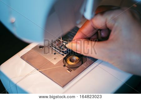 Machine sewing, hand in the process of sewing the fabric on the machine