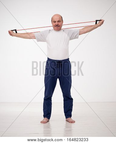 Elderly man goes in for sports with the exerciser expander. Exercise to strengthen muscles