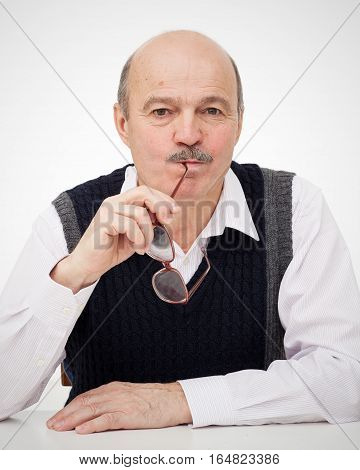 Elderly Bald Man With A Mustache Sitting At The Table And Eats Eyeglasses. Stupid Habit Of Taking Th