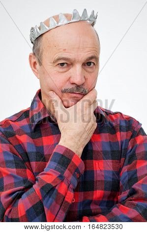Elderly Man With A Paper Toy Crown Stands With Folded Hands On His Head. Thoughtful Look Forward.