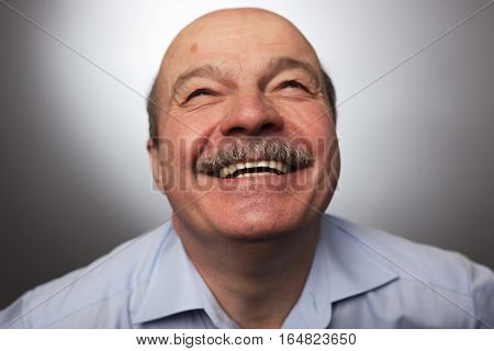 Elderly man laughs from ear to ear giggles on the funny stories. Eyes closed. Be happy of news or events