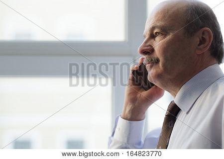 Elderly Man In A Tie Carefully Listen To The Interlocutor On The Phone. Unhappy Looking Away.