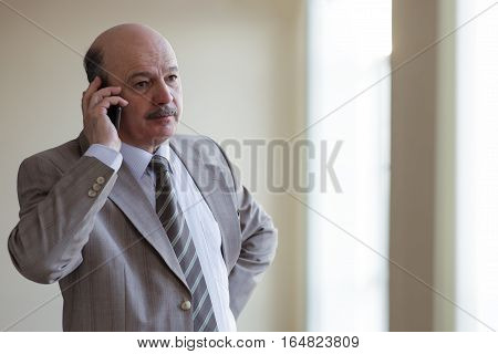 Man In Suit Talking On The Phone, Solving Important Questions. Negotiations In Office Corridor