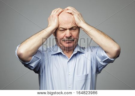 Old man put his head in his hands, suffering from migraine. Suffering from a headache, or a multitude of problems