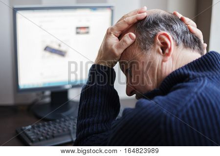 Elderly man wearily turns his head away from the monitor. Tired of using the Internet.