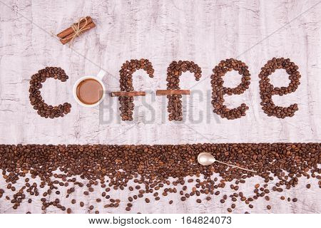 Coffee. Letters from coffee grains. An inscription from coffee grains. Coffee grains on a concrete background