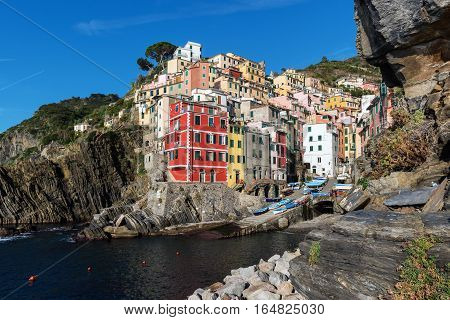 Houses on rocks near sea bay of Riomaggiore town in Cinque Terre national park in Italy