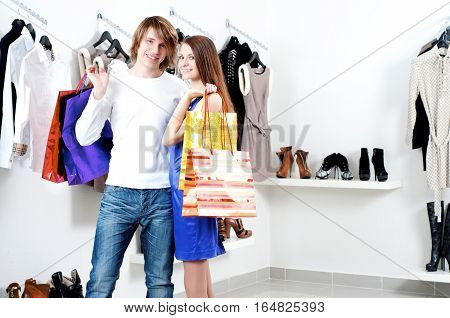 cute man and the woman in shop choose clothes