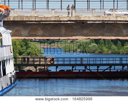 UGLICH RUSSIA - JUNE 2016: Passenger ship in navigable gateway of Uglich hydroelectric power station on river Volga. The rise of the vessel in the lock chamber difference of water the bridge over the gateway with cars and pedestrians