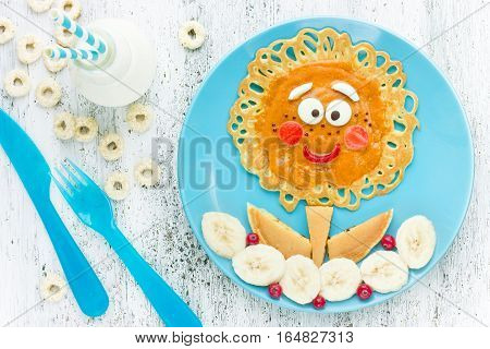 Cute flower pancakes with banana for kids breakfast. Good morning concept creative idea for fun children food