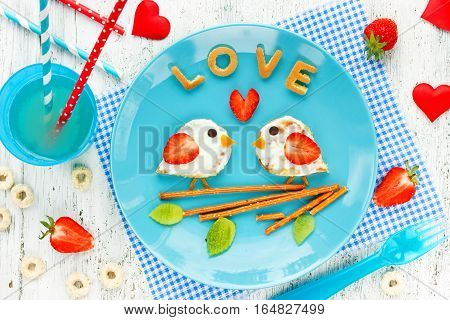 Love birds pancakes - romantic breakfast on Valentines Day. Creative idea for kids breakfast - funny pancakes shaped cute birds with cream and strawberry
