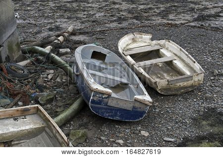 Two old beached wooden rowing boats white and blue, weathered and beaten on the shore