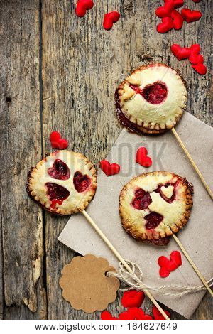 Homemade shortbread cookies on stick or pie pops with strawberry jam on wooden background - dessert idea on Valentines Day