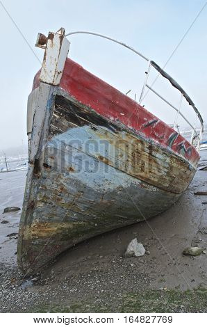 Burnt out ship wreck, boat fire damage, beached on sandy shore line, fishing boat, pealed paint