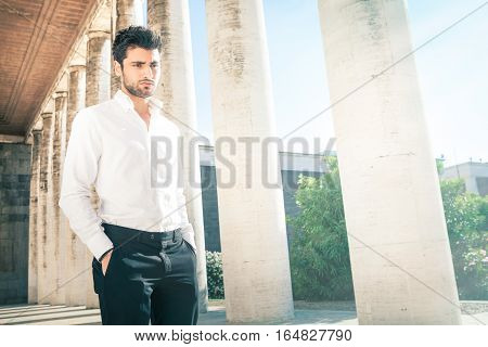 Handsome young elegant man outdoors. Nervous and pensive. A beautiful Italian man is walking with his hands in his pockets, near an ancient colonnade outdoors. His gaze is pensive and thoughtful. White shirt and blacks pants.